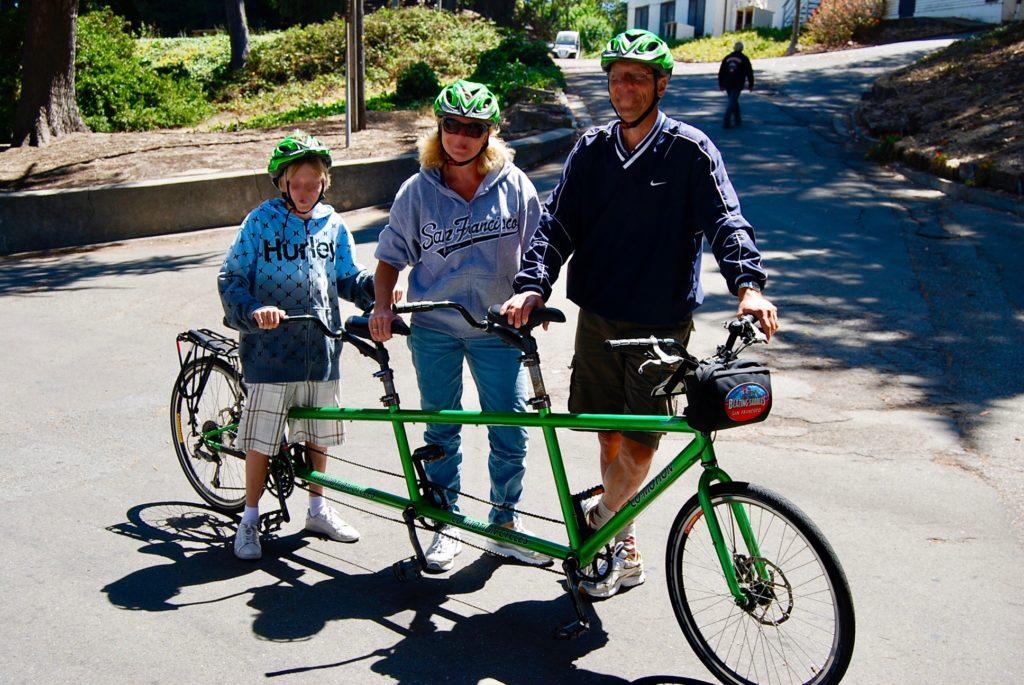 3人乗り自転車でサイクリングを楽しむ親子の写真