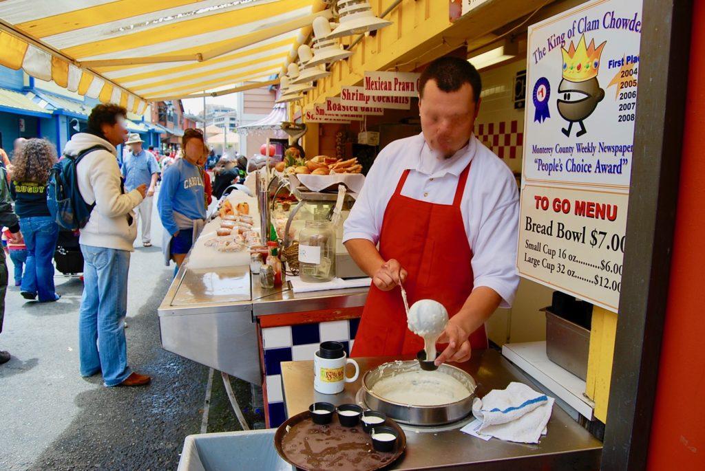 オールドフィッシャーマンズワーフでクラムチャウダーの試食用カップにスープを入れるお店のスタッフ