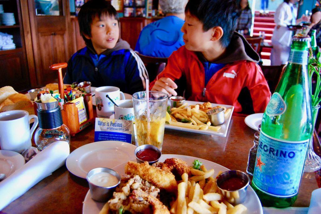 オールドフィッシャーマンズワーフのシーフードレンストランで食事をする子供達