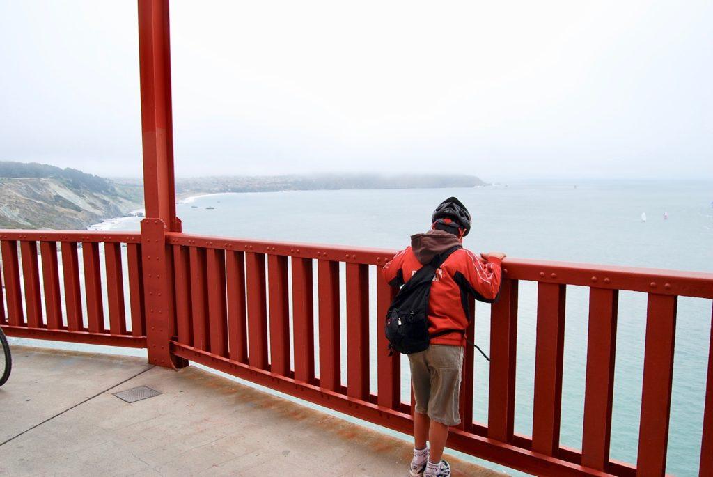 橋の中間地点の休憩スペースで海面を見下ろす長男