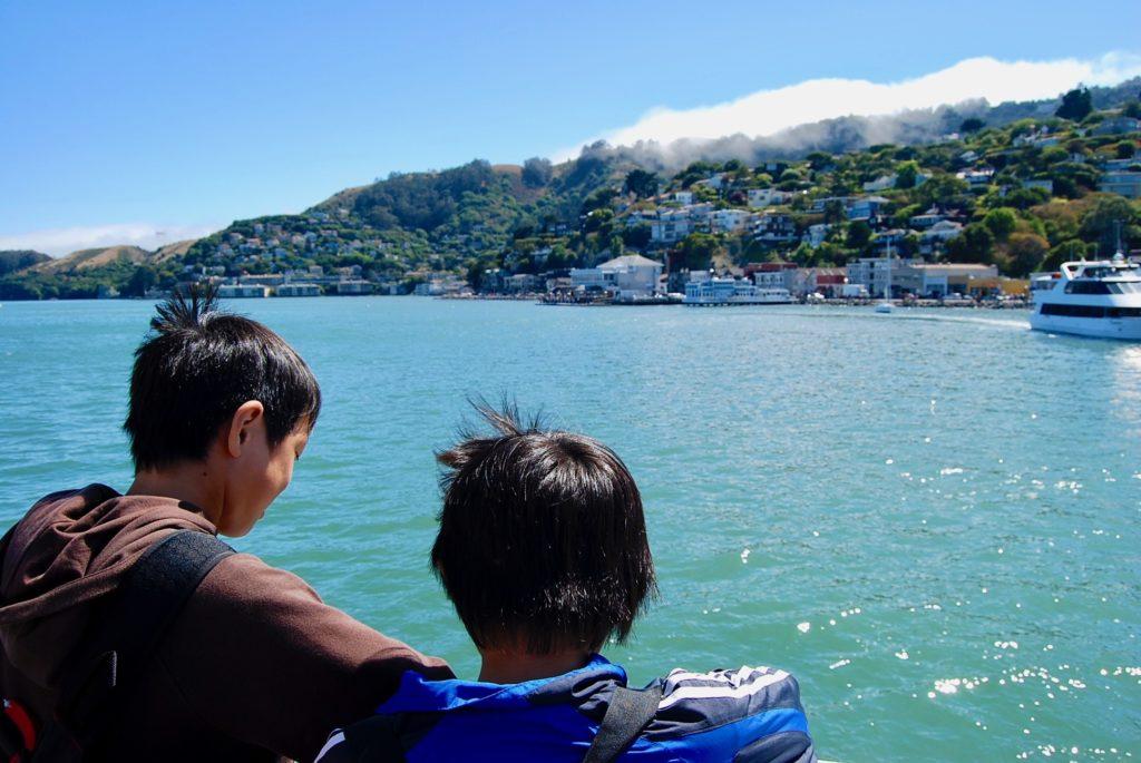 遠ざかるサウサリートの街並みを船上から眺める子供達