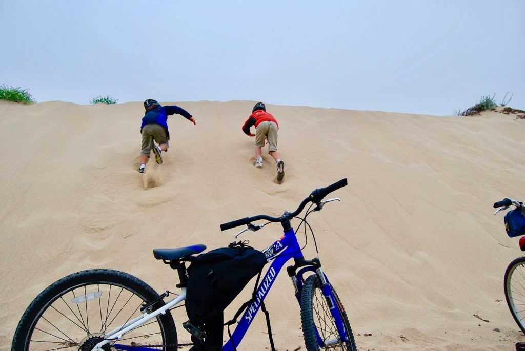 自転車を止めて砂の坂を駆け上る子供たち