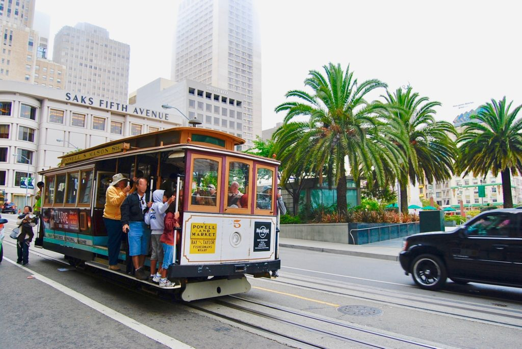 観光客を乗せてサンフランシスコのビル街を走るケーブルカー
