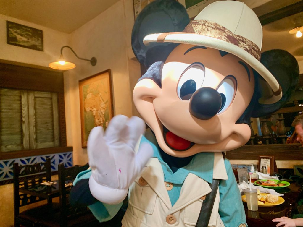 テーブル席に来て手を振るミッキーマウス