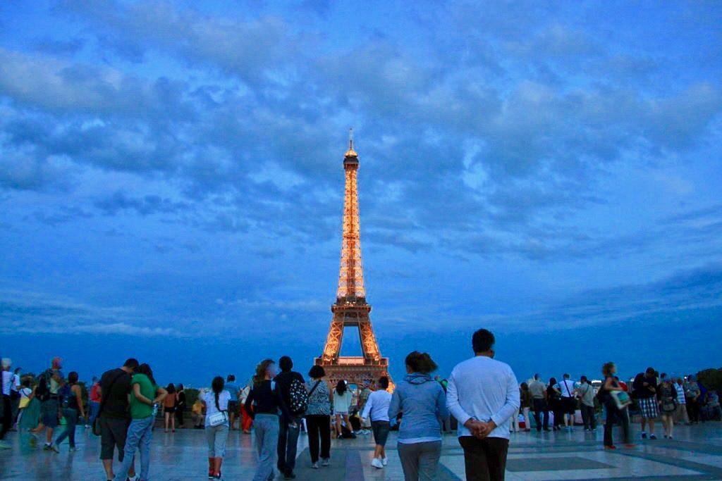 シャイヨー宮殿からライトアップされたエッフェル塔を眺める大勢の観光客