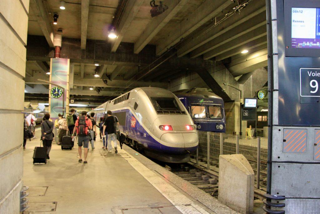 モンパルナス駅のホームに停車しているTVGとホームを荷物を持って歩く乗客たち