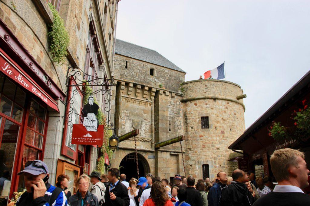 モンサンミッシェル名物のオムレツ屋さんの赤い看板と城壁の下をくぐる3つ目の城門