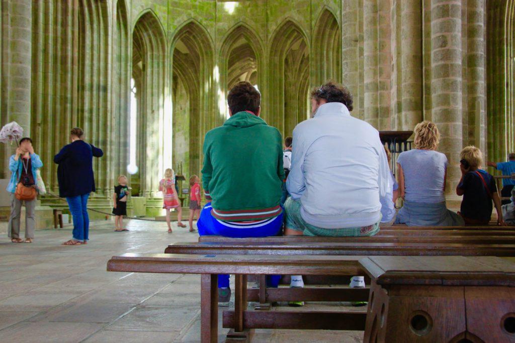 礼拝堂のベンチで休む観光客たち