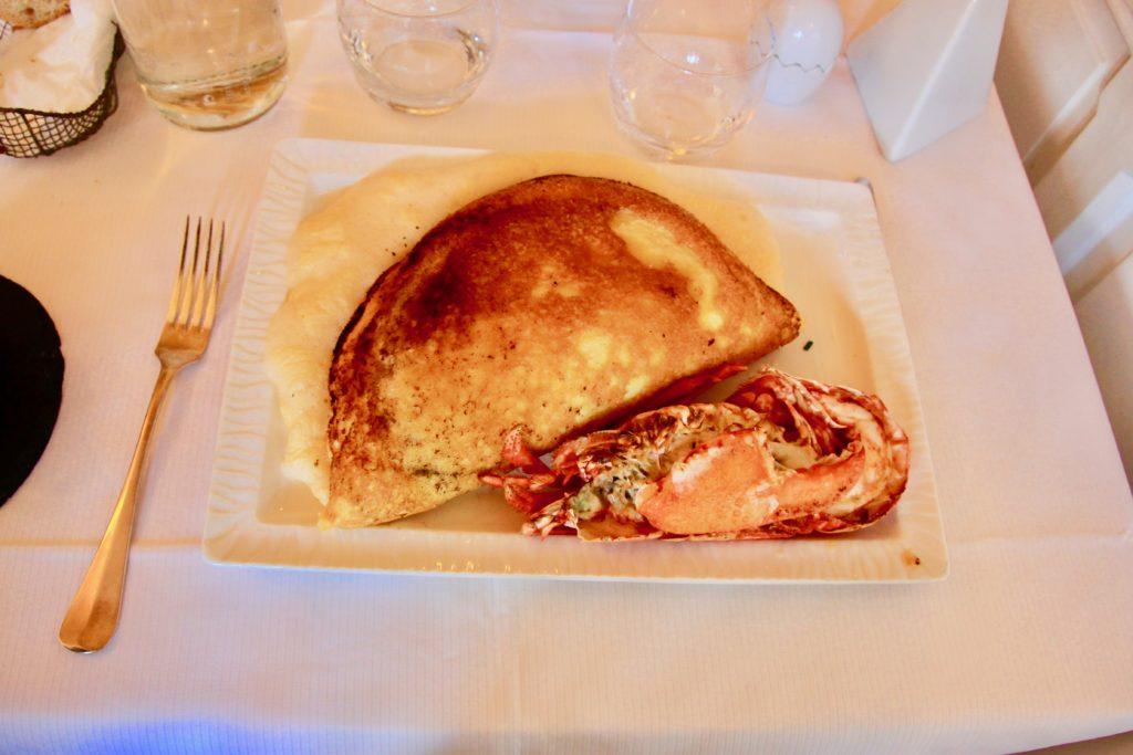 テーブルに運ばれた白い皿に盛られているオマールエビとモンサンミッシェルオムレツ