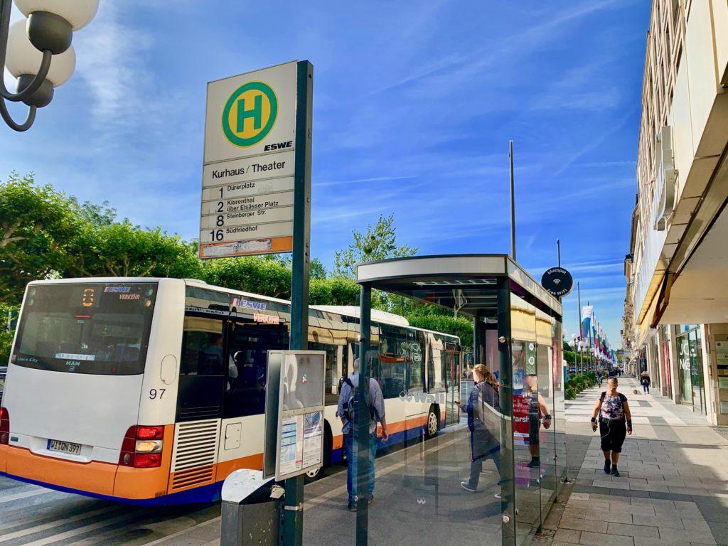 ヴィルヘルム通りのバス停でバスに乗る人