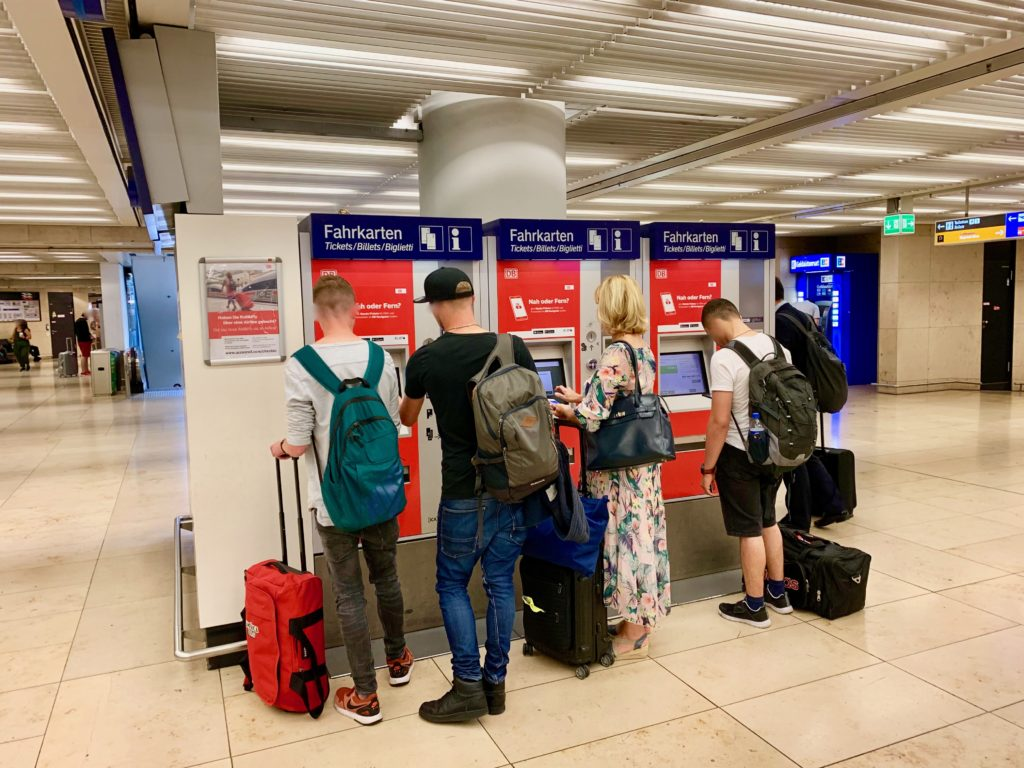 鉄道駅コンコースの自動券売機で乗車切符を買う人たち