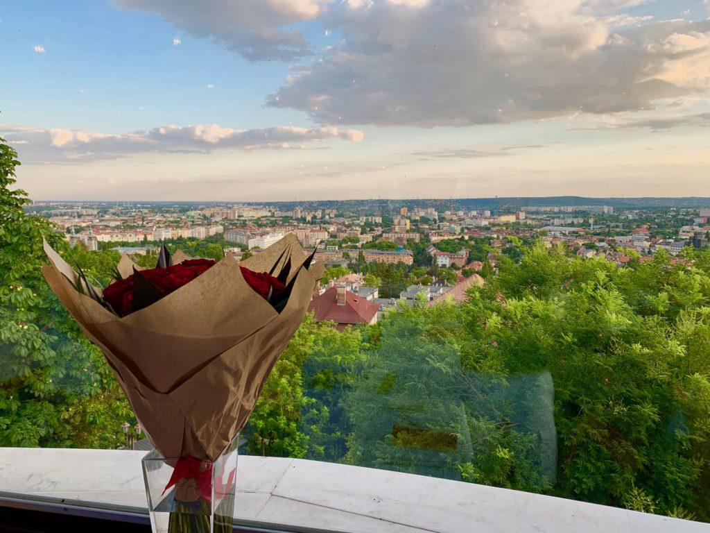 窓際に置かれた赤いバラの花束とブダペストの夕焼けの街並み