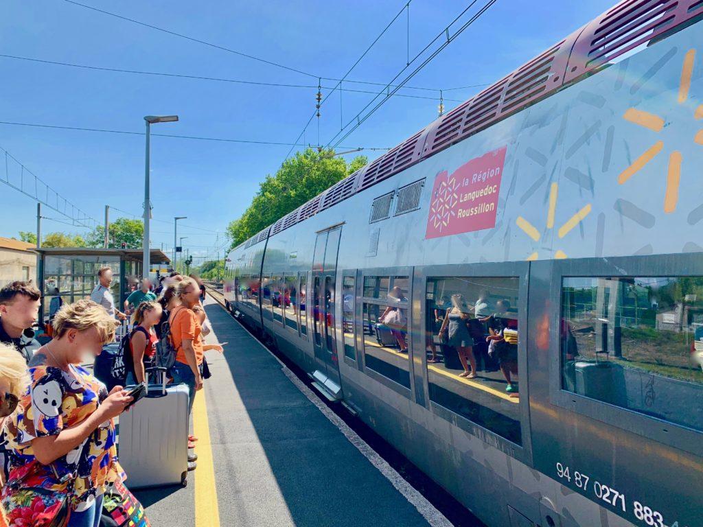 アグド駅のホームで列車の到着を待つ乗客