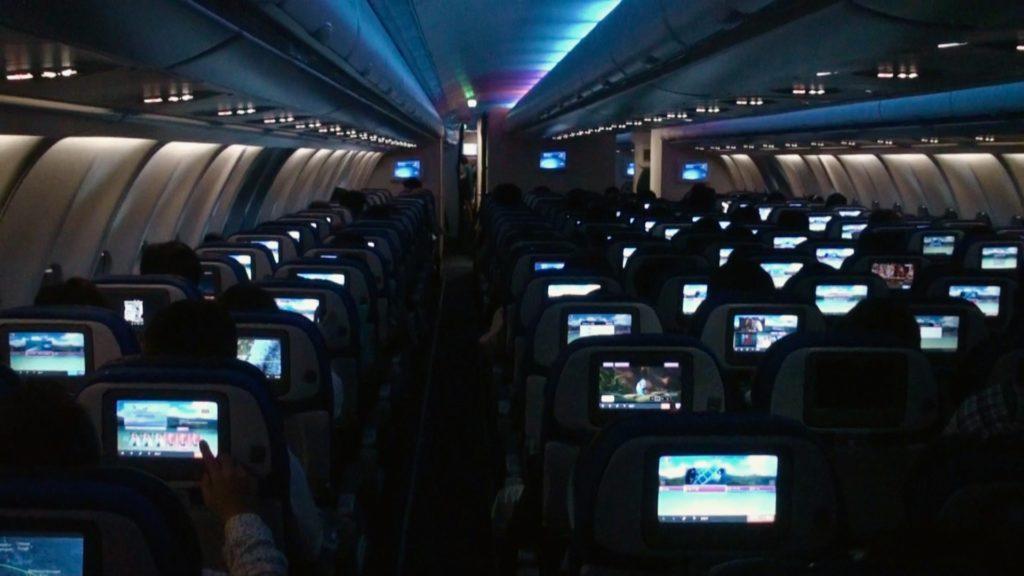 消灯して暗くなったハワイ行きの機内