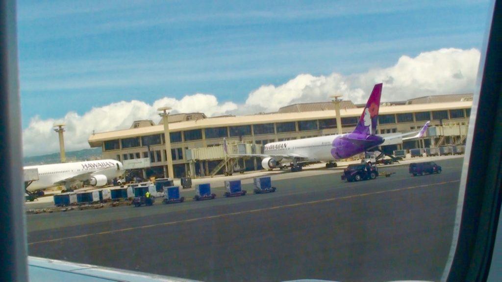 ホノルル国際空港の滑走路。ターミナルビルにハワイアン航空の飛行機が止まっている。