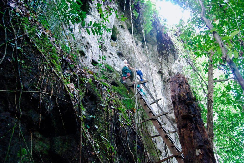 岩壁の遺跡に設けられた急階段の櫓を登る子供達