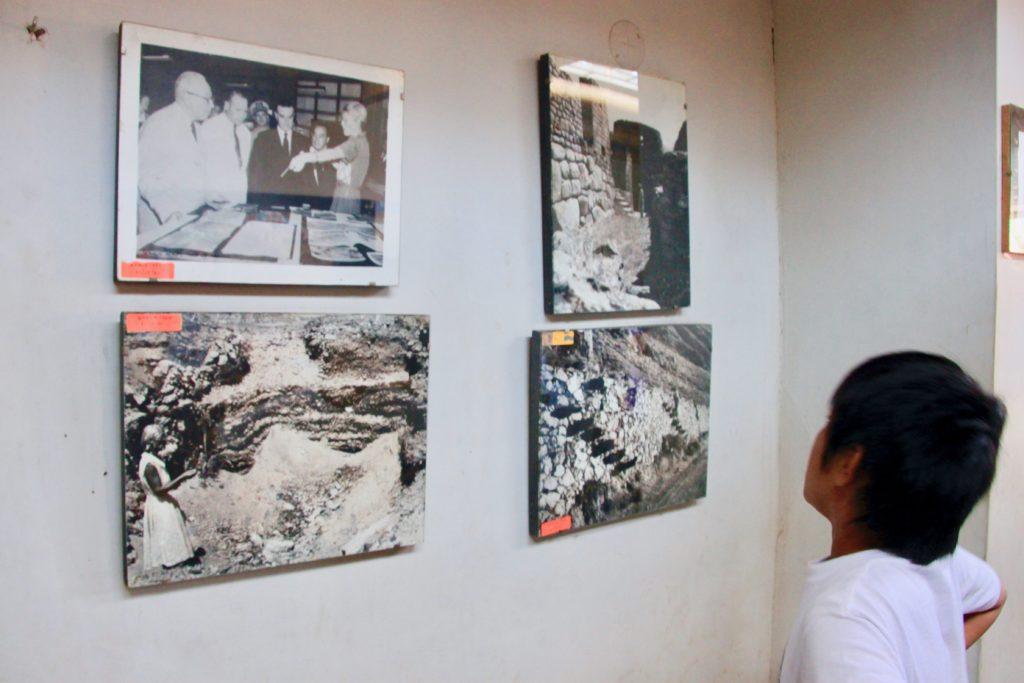 壁にかかった研究、保護活動の古い写真を見つめる次男