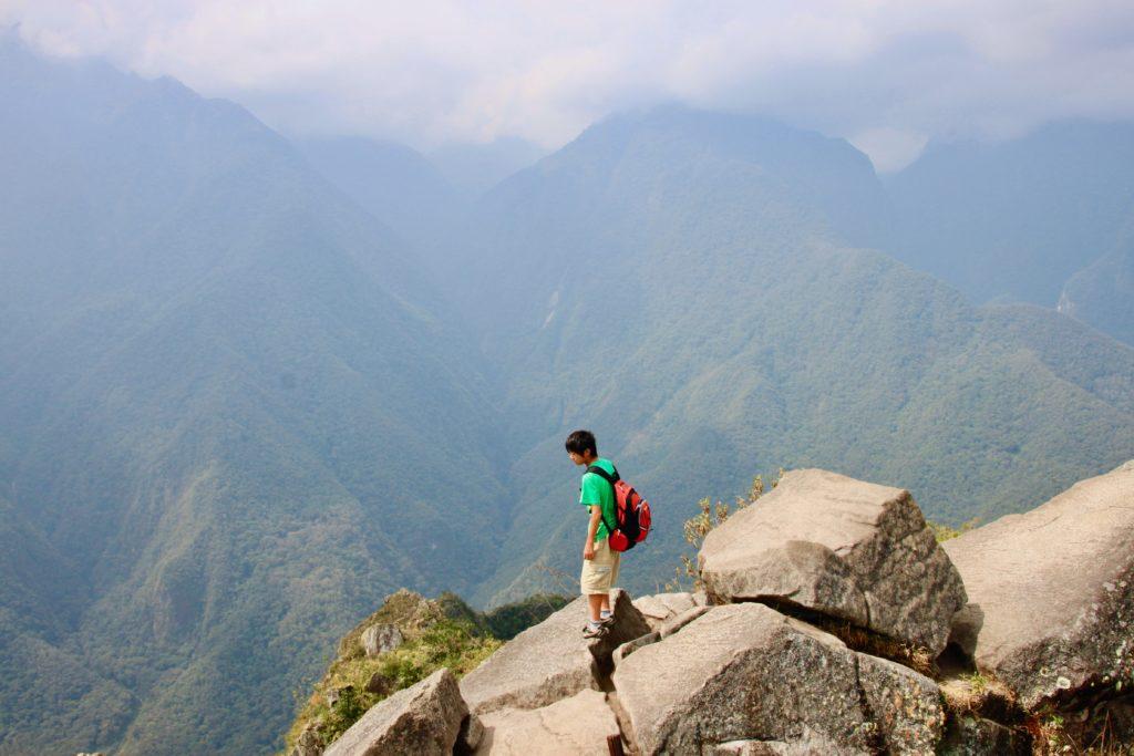 ワイナピチュの山頂の岩場に立つ長男