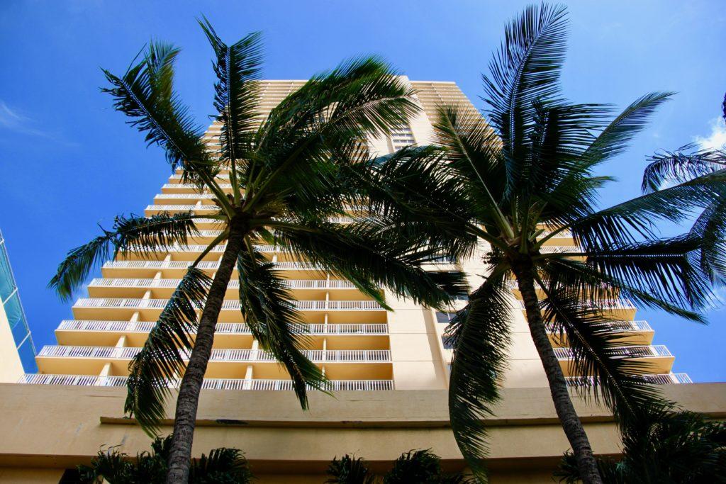 正面から見上げたアロヒラニ・リゾート・ワイキキ・ビーチの外観とヤシの木