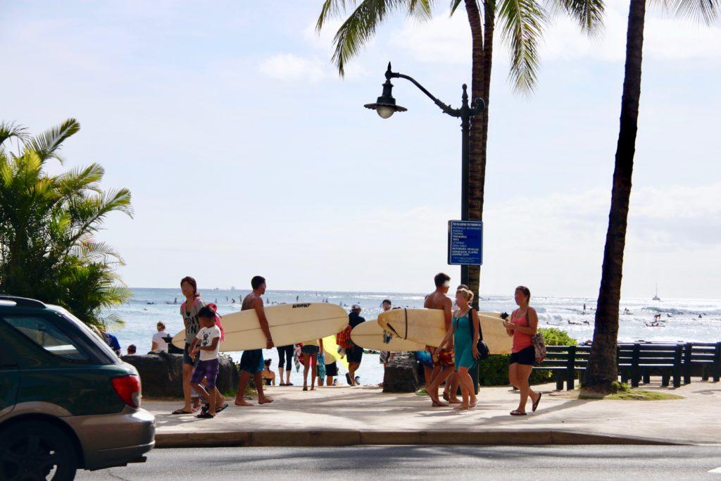 ワイキキビーチの歩道をサーフボードを持って歩く人たち