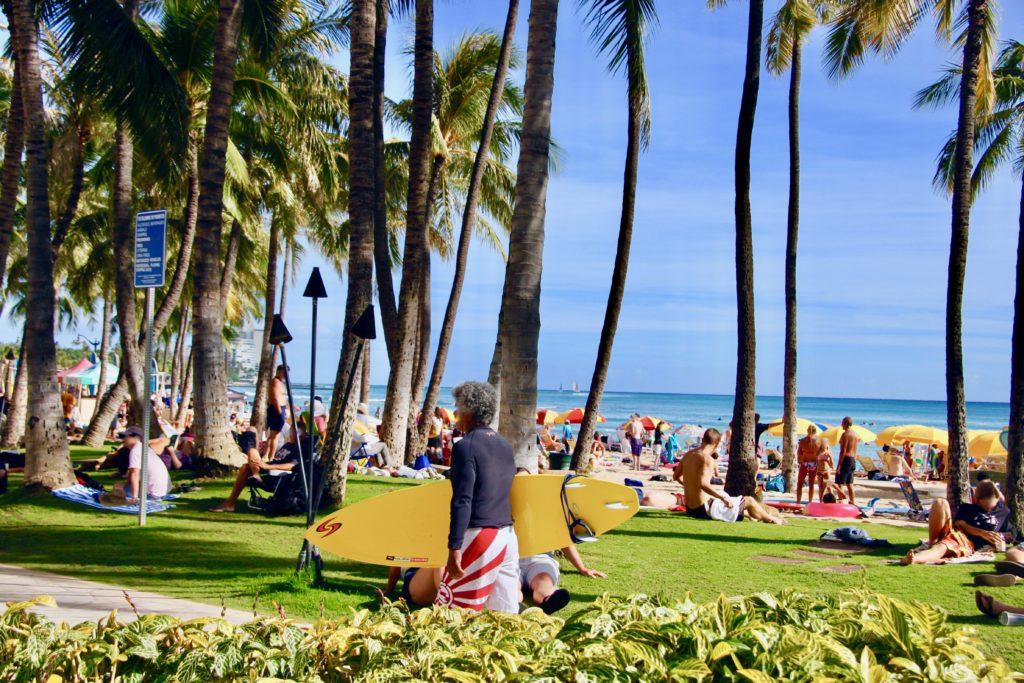 ワイキキビーチでくつろぐ大勢の人たちとヤシの木と青い海