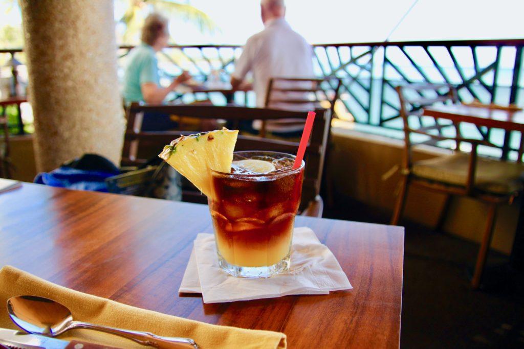 グラスにパイナップルの切れ端と赤いストローが差してあるマイタイ