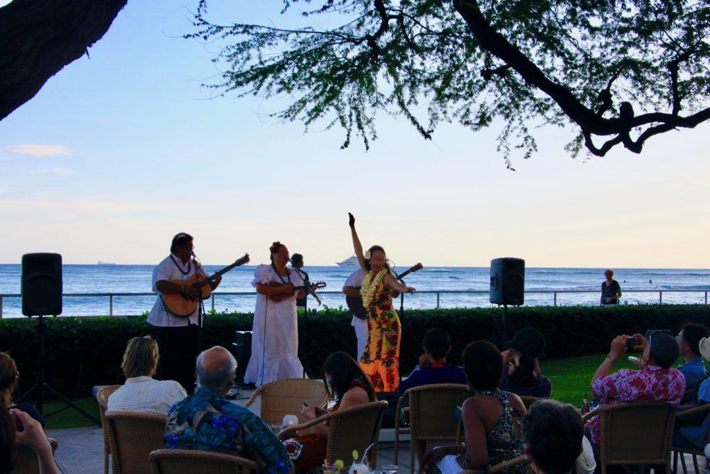 海を背景にしたフラダンスショーを見学するお客たち