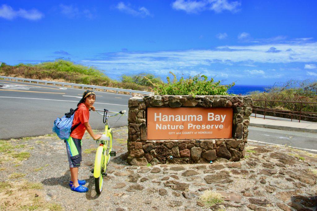 ハナウマ湾自然保護区の看板の前で自転車を止めて立つ次男