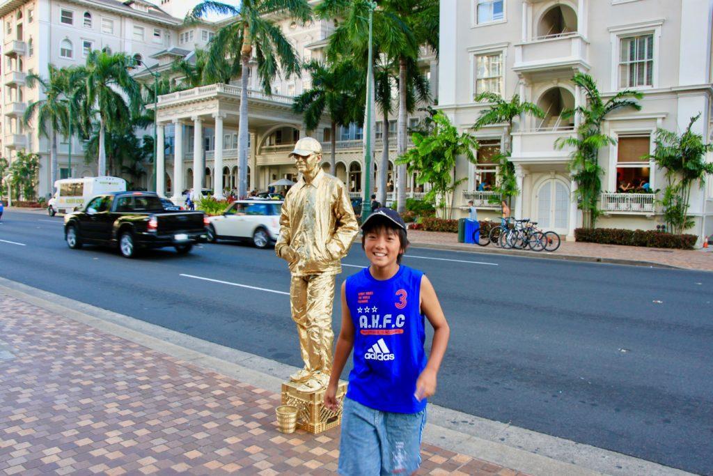 カラカウア大通りのゴールドの大道芸人と次男