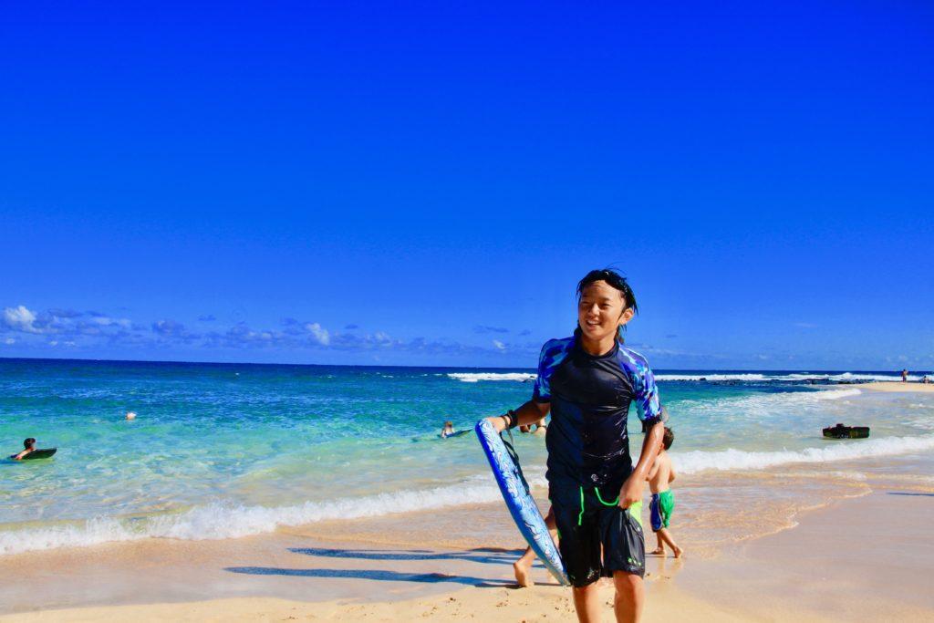 ビーチでボディボードを持って嬉しそうに笑う次男