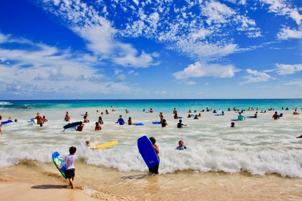 遠浅のビーチでボディボードをする大勢の人