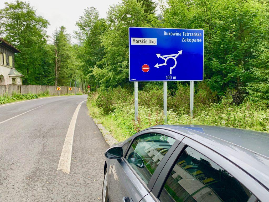 国境の手間に止めた車と道路標識