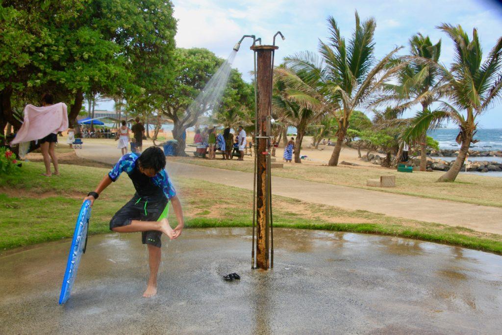 シャワーで足の砂を落とす次男