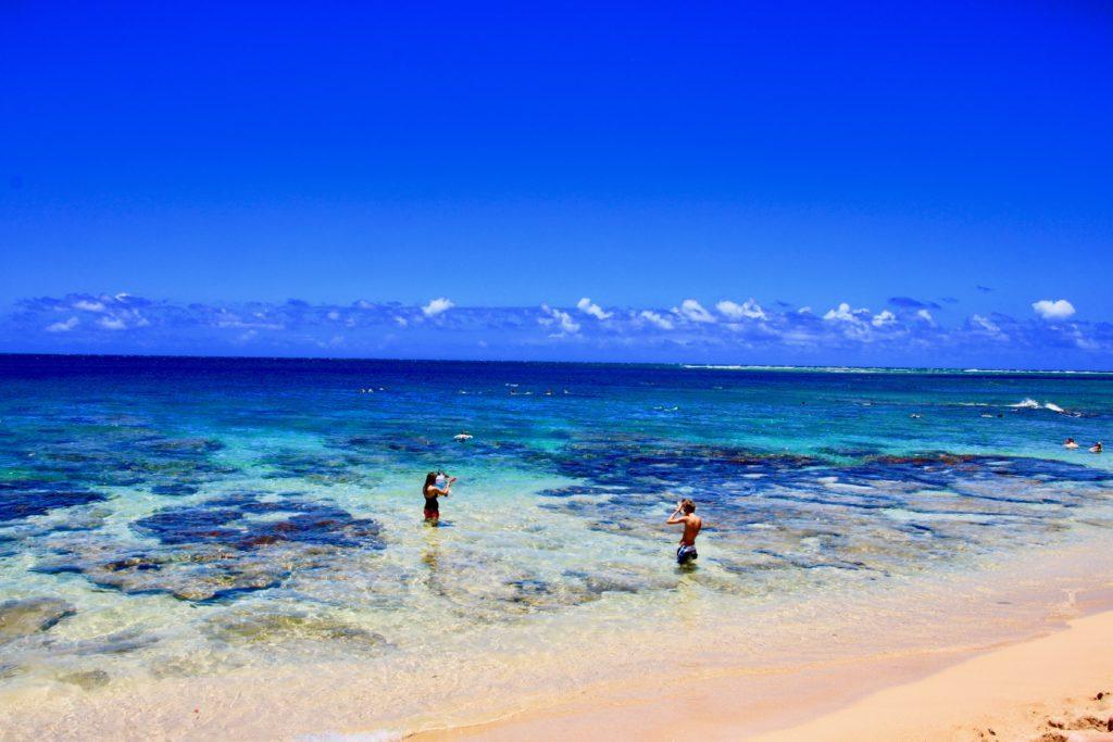 トンネルビーチの珊瑚礁でシュノーケリングを楽しむ人たち