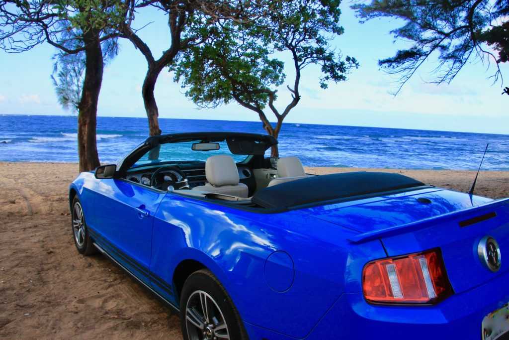 ビーチの木陰に止めた青いオープンカー