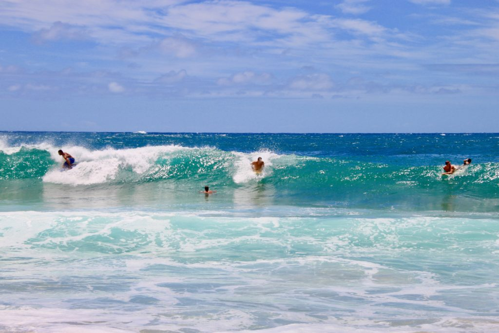 シップレックビーチの波でサーフィンやボディボードをする人