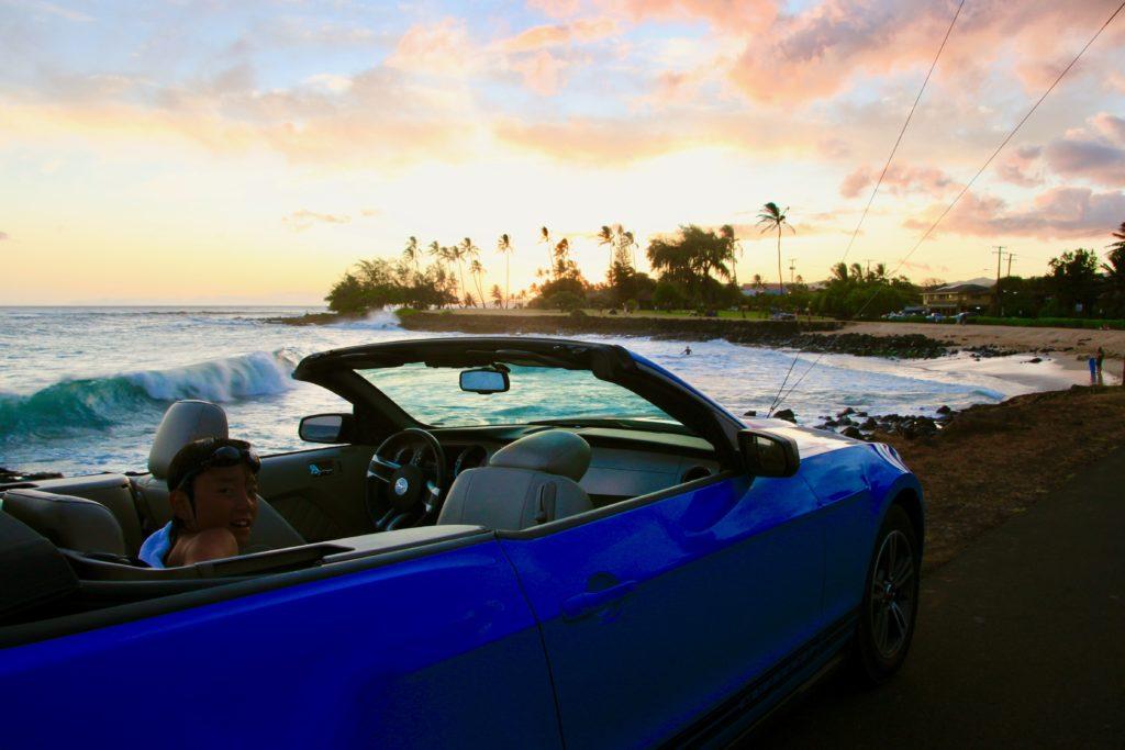 カウアイ島の夕焼けを見ながらオープンカーから顔を出す次男
