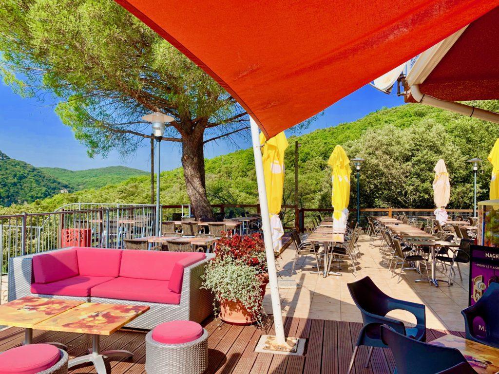 黄色いパラソルや赤いタープが貼られたレストランのテラス席