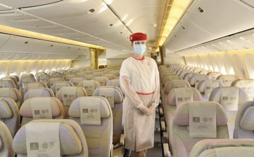 機内のシートとマスクをしたキャビンアテンダントさん