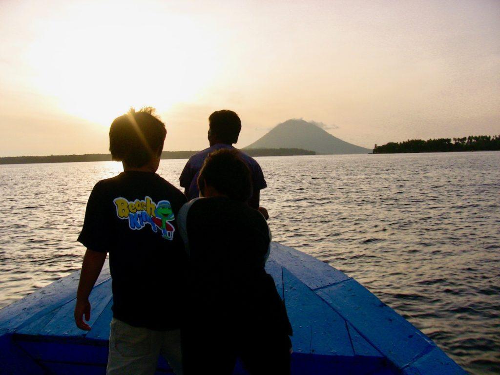ボートに乗る子供達とブナケン島に傾く夕日