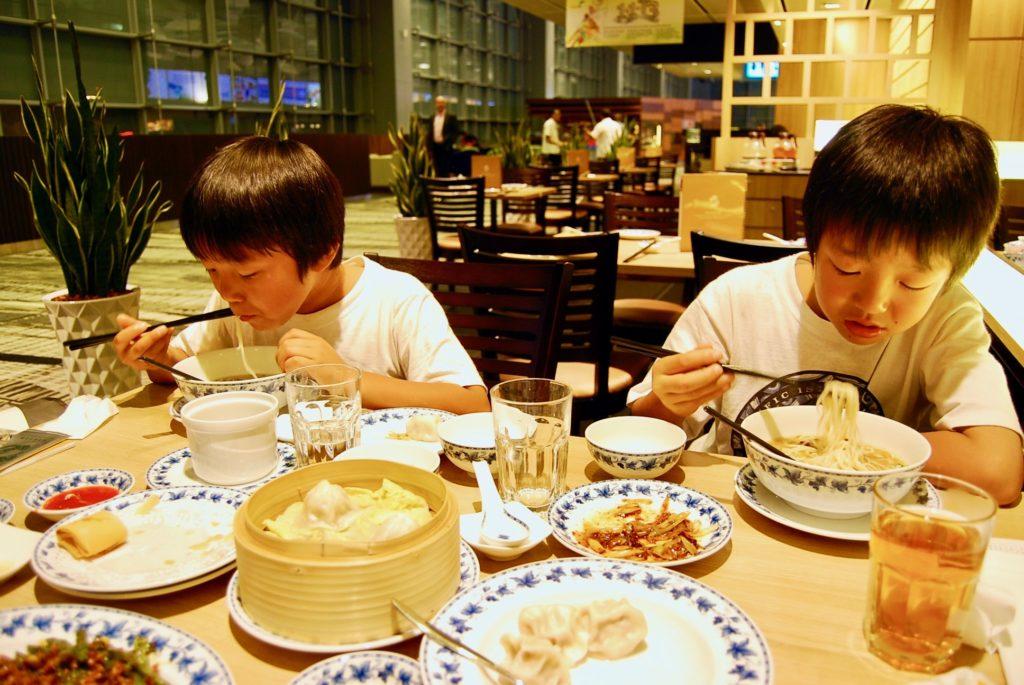 チャンギ国際空港のクリスタルジェイドで食事をする子供達