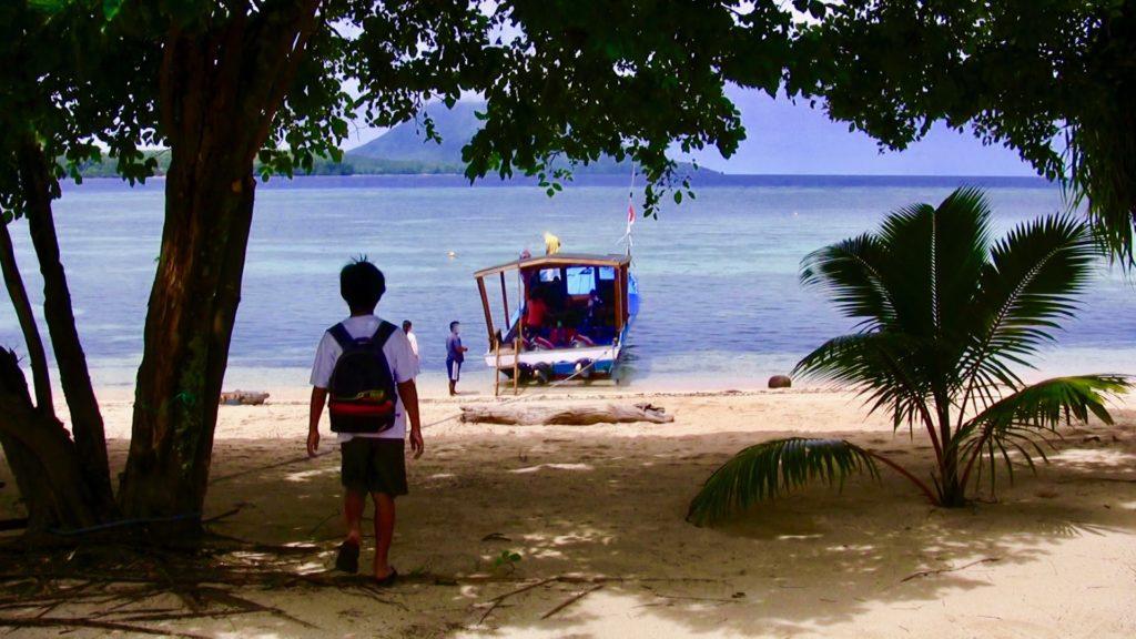 ビーチに停泊している送迎ボートに向かって歩く寂しそうな長男の背中