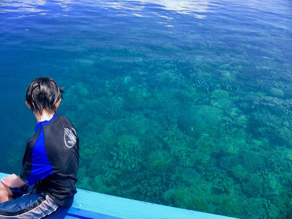 ボートの淵に座って珊瑚礁を見下ろす長男