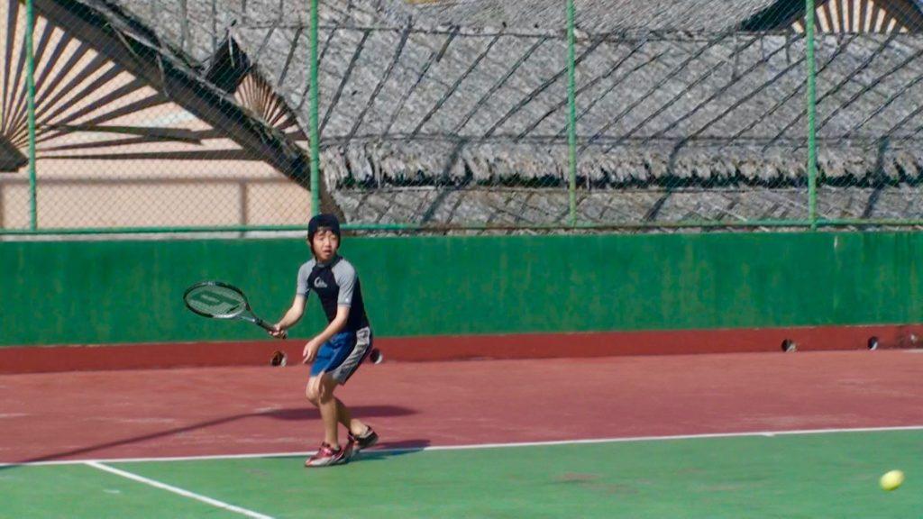ホテルのコートでテニスをする長男