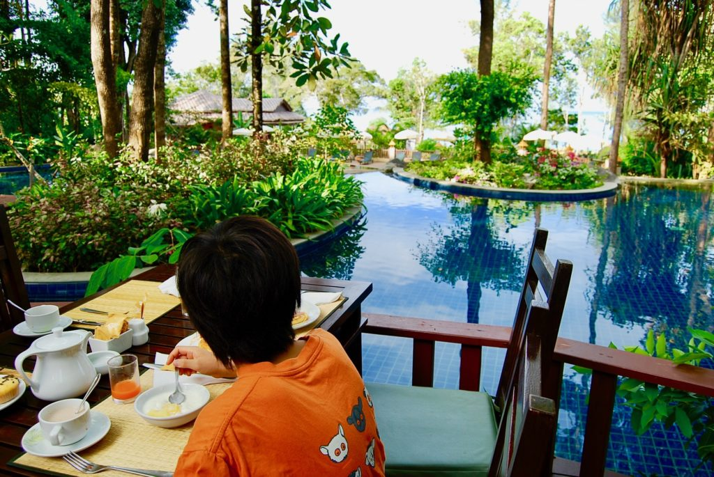 プールサイドのテラス席で朝食を食べる長男