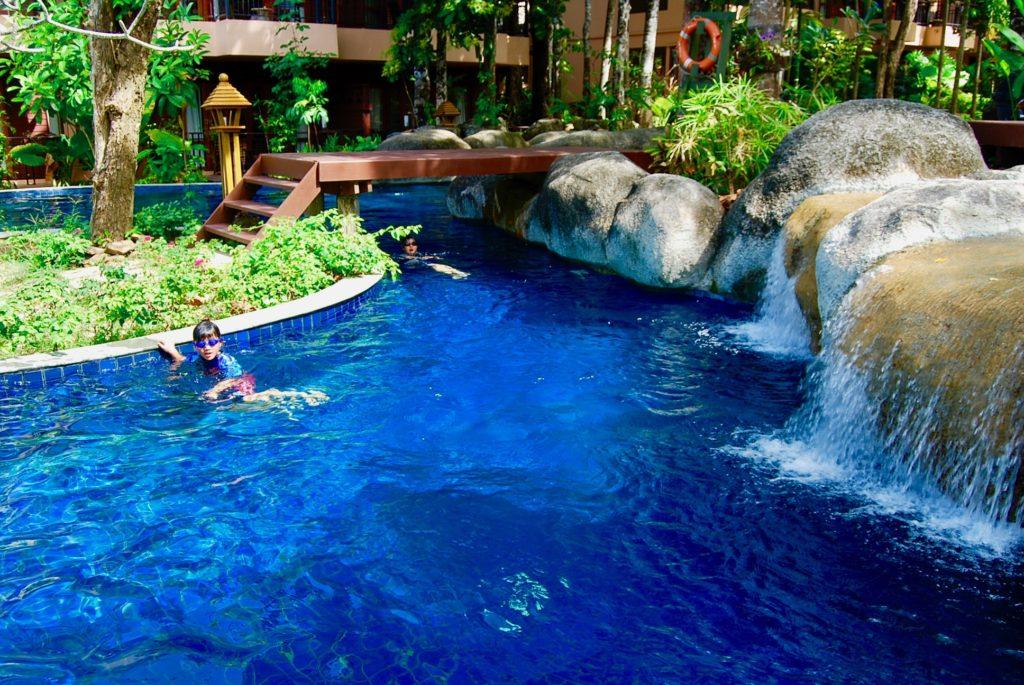 滝のあるプールで遊ぶ子供たち