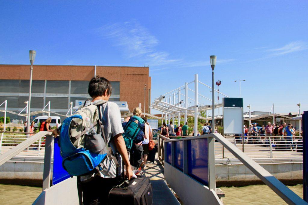 空港の水上バス乗り場で下船して荷物を引っ張る次男
