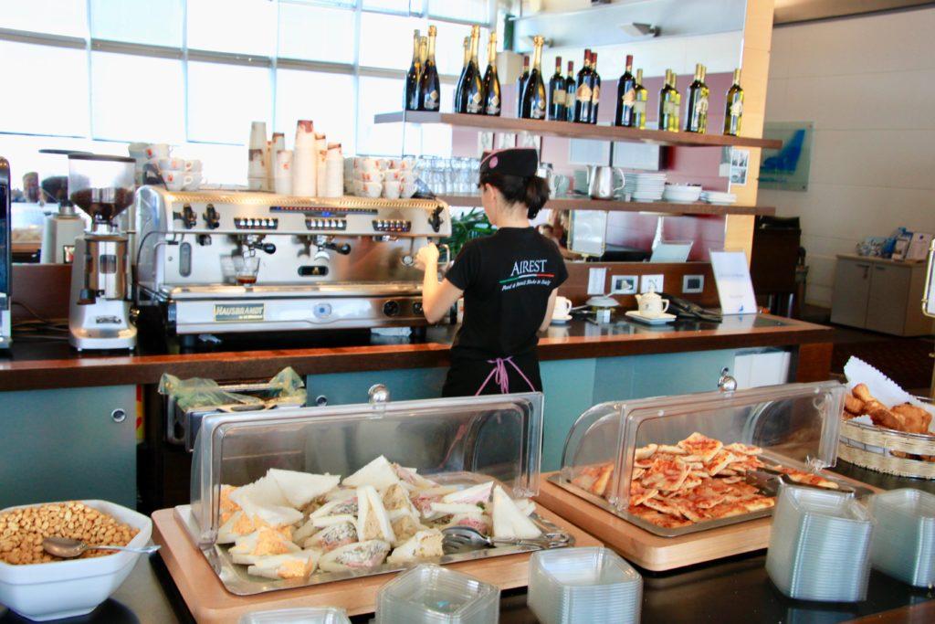 カフェマシーンでカプチーノを入れる女性