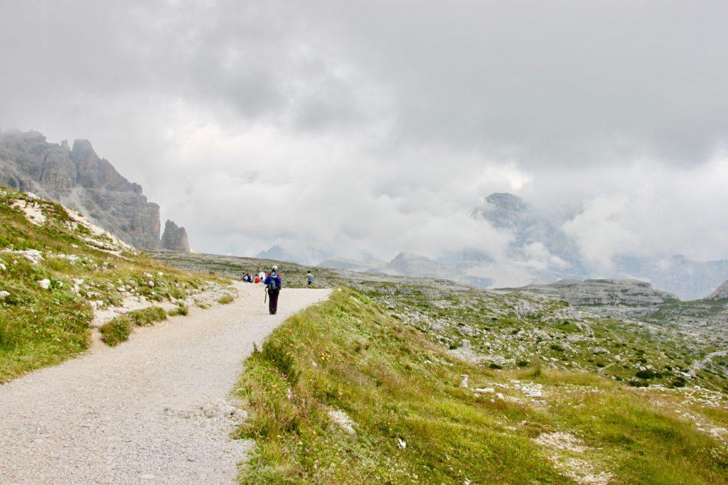 カルスト台地のような景色の中でトレッキングを楽しむ家族連れの後ろ姿