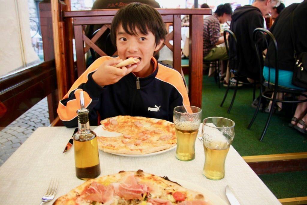コルチナダンペッツォのピッツェリアで大きなピザをほうばる次男